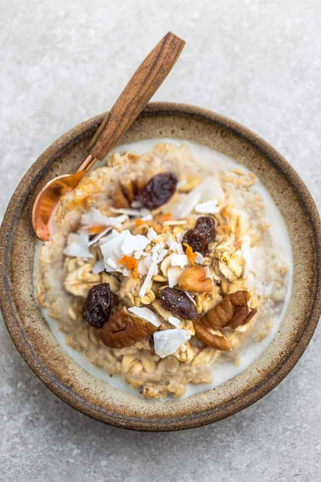 carrot cake oatmeal in brown bowl with raisins and coconut flakes