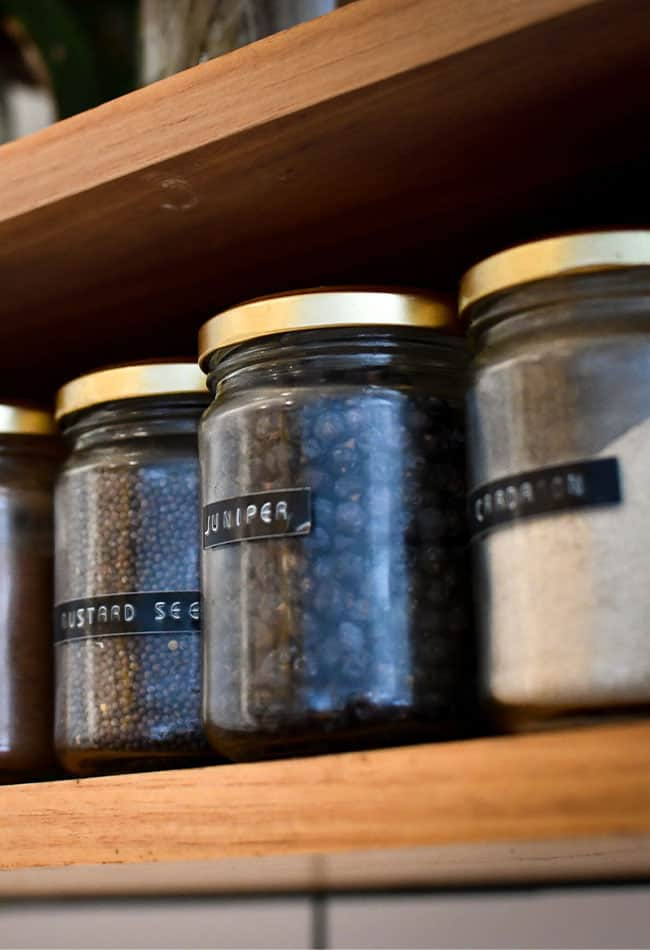 jars filled with spices on wooden shelf for pantry