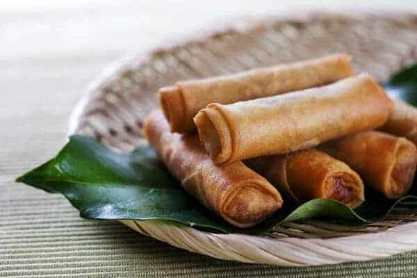 Fried Chinese Spring Rolls stacked on a large green leaf on a plate