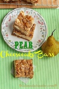 Pear Cheesecake Bars stacked on a plate next to another bar and a whole pear