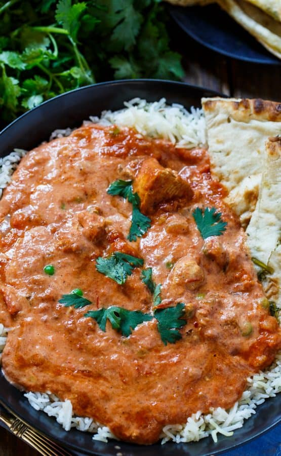 A plate of Chicken Tikka Masala over rice with pita bread